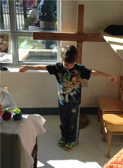 FDK child showing how Jesus is on the Cross