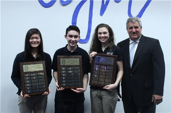 Mr. Power stands with three UCC students, each of whom are holding awards.