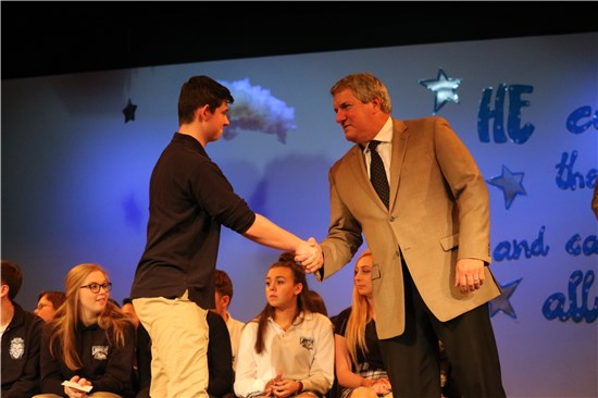 A photograph of Mr. Power shaking hands with a student at the 2016-17 Academic Assembly.
