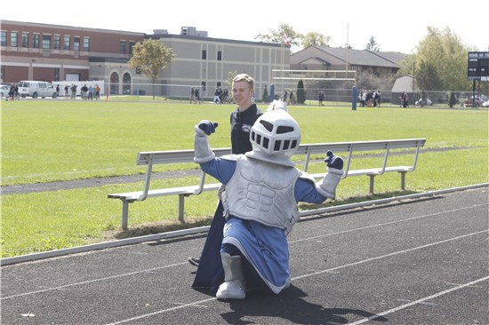Ucc's mascot, Lance, appears on the track with a student.