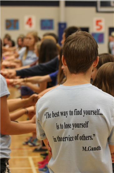"A photograph of students. In the foreground we see the back of a teenage boy, wearing a shirt that reads ""The best way to find yourself...is to lose yourself in the service of others - M.Gandhi"". In the background there are students arranged  in two rows, holding hands across the gap between rows."